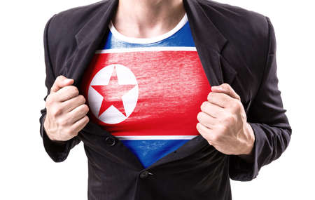 Businessman stretching suit with North Korea flag on white background Stock Photo