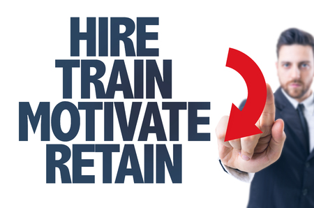 retain: Business man pointing the text: Hire train motivate retain Stock Photo