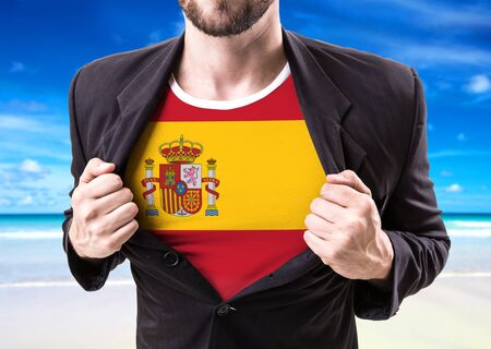Businessman stretching suit with Spain flag on beach background