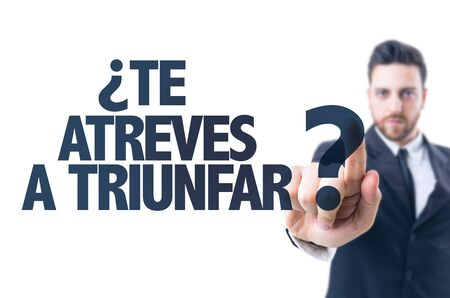 Business man pointing the text: Te atreves a triunfar (dare you to success in Spanish)