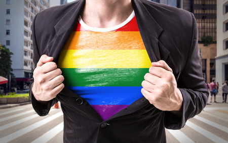 nationalism: Businessman stretching suit with rainbow flag in Paulista Avenue, Sao Paulo, Brazil background Stock Photo