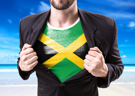 Businessman stretching suit with Jamaica flag on beach background