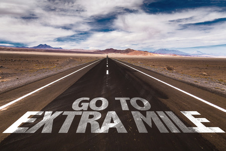 strong message: Go to extra mile written on the road Stock Photo