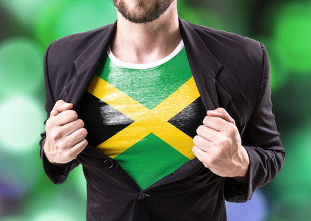 Businessman stretching suit with Jamaica flag on bokeh background
