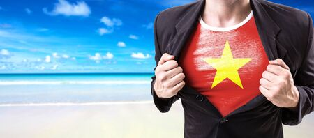 Businessman stretching suit with Vietnam flag on beach background Stock Photo