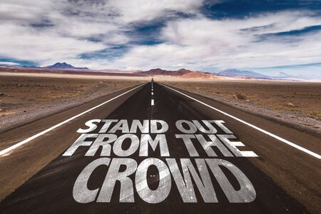stand out: Stand out from the crowd written on the road Stock Photo