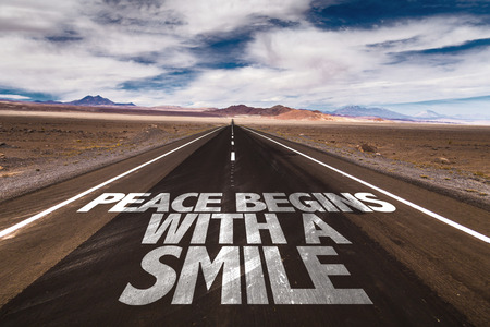 highway love: Peace begins with a smile written on the road Stock Photo