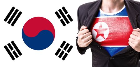 Businessman stretching suit with North Korea flag on South Korea flag background