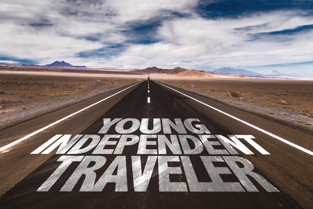 independent: Young independent traveller written on the road Stock Photo