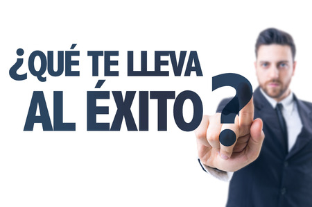 Business man pointing the text: Que te lleva al exito al exito? (What leads you to success? in Spanish)