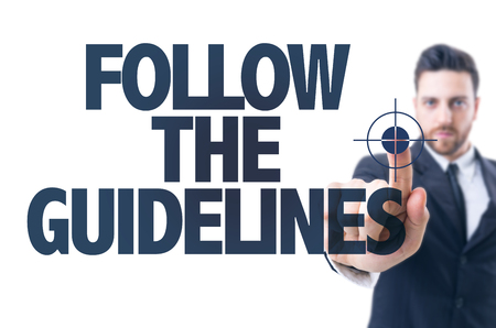 conform: Business man pointing the text: Follow the guidelines Stock Photo