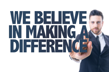 strive: Business man pointing the text: We believe in making a difference