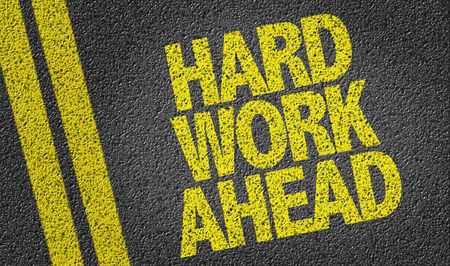 Text on tar road: Hard work ahead Stock Photo