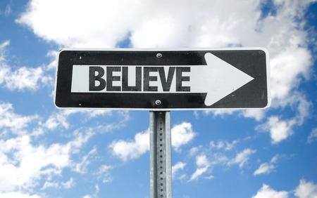 creer: Believe sign with arrow on sunny background Foto de archivo