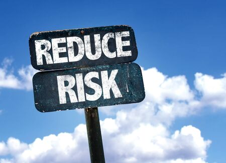 reduce risk: Reduce risk written on the road sign with clouds and sky background