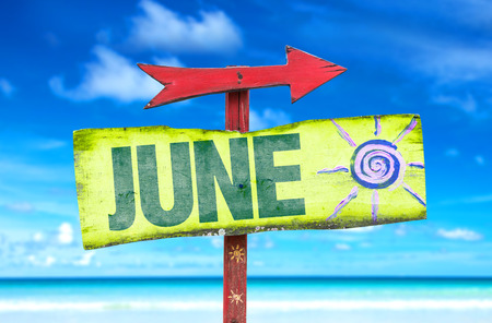 June sign with arrow on beach background