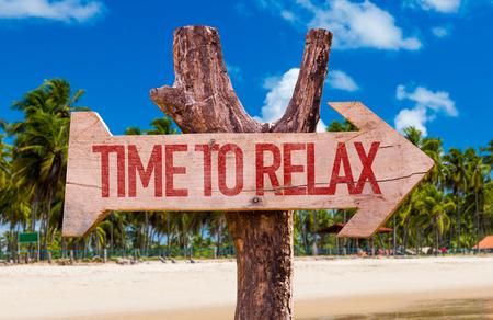 Tijd om te ontspannen bord met pijl op het strand achtergrond Stockfoto