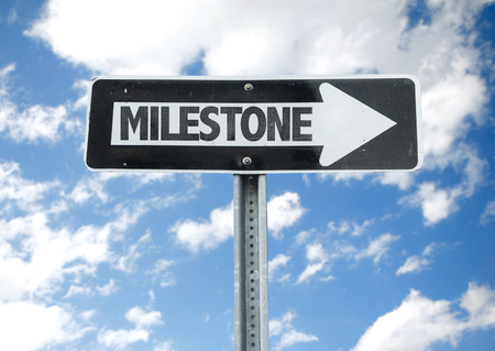 milestone: Milestone sign with arrow on sunny background