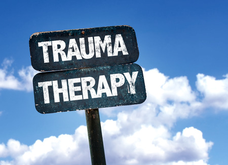 Trauma therapy written on the road sign with clouds and sky background