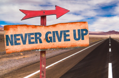 Never give up sign with arrow on a highway background
