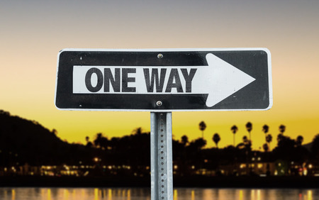 one way sign: One way sign with arrow on sunset background Stock Photo