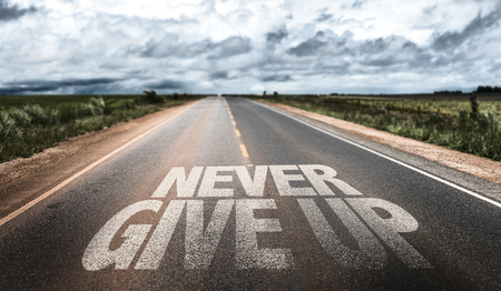 Never give up written on the road