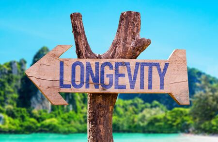 water quality: Longevity sign with arrow on beach background Stock Photo