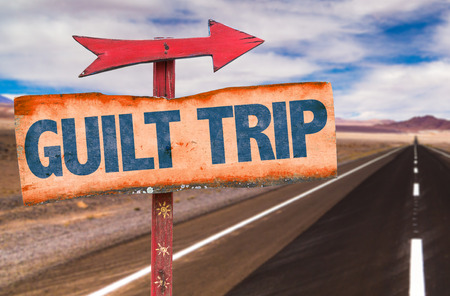 Guilt trip sign with arrow on a highway background