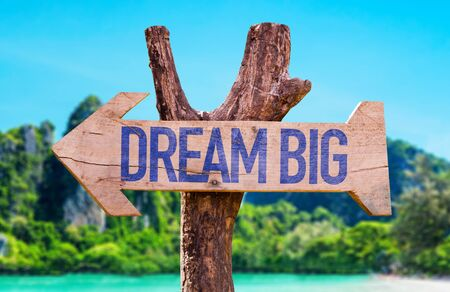 Dream big sign with arrow on beach background