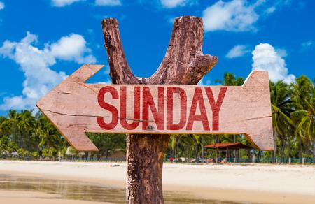 Sunday sign with arrow on beach background
