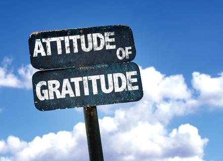 Actitud de agradecimiento escrito en la señal de tráfico con las nubes y el cielo de fondo