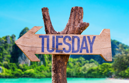 Tuesday sign with arrow on beach background