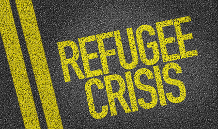 exile: Text on tar road: Refugee crisis Stock Photo