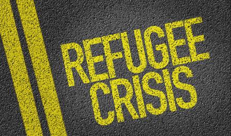 housing crisis: Text on tar road: Refugee crisis Stock Photo