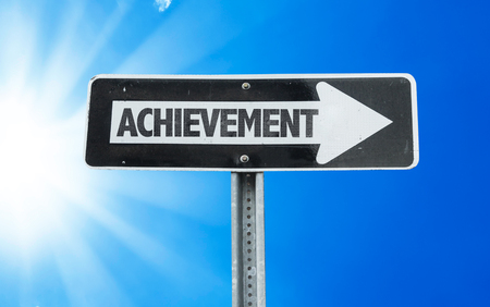 achiever: Achievement sign with arrow on sunny background Stock Photo