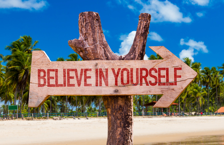 Believe in yourself sign with arrow on beach background Stock Photo