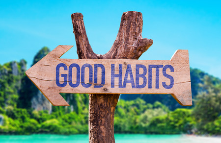 good habits: Good habits sign with arrow on beach background Stock Photo