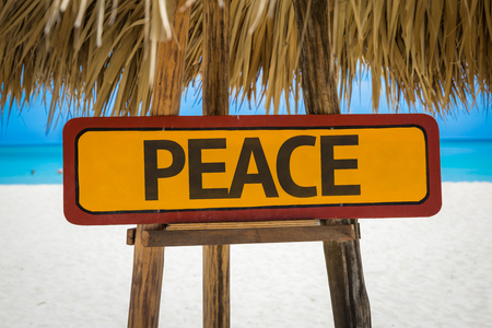 redemption of the world: Wooden sign board in beach with text: Peace Stock Photo