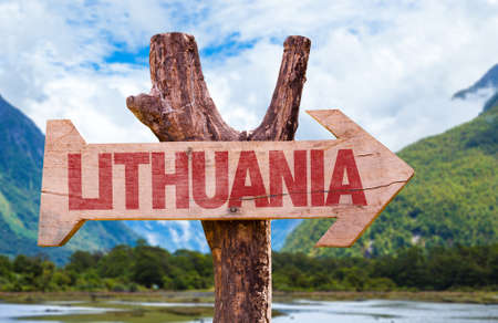 Wooden sign board in wetland with text: Lithuania