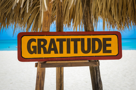 thankfulness: Wooden sign board in beach with text: Gratitude