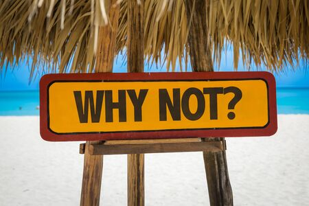 why not: Wooden sign board in beach with text: Why not? Stock Photo