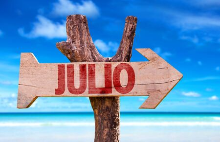 Julio (July in Spanish) sign with arrow on beach background
