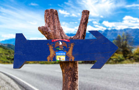 Michigan flag sign with arrow on road background Stock Photo