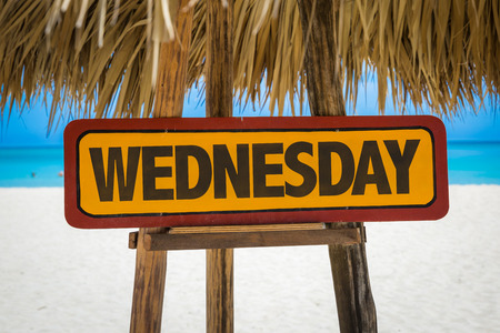 wednesday: Wooden sign board in beach with text: Wednesday