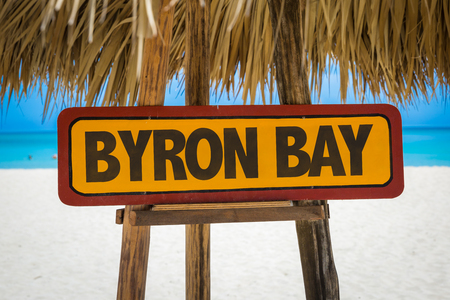 Wooden sign board in beach with text: Byron Bay Archivio Fotografico
