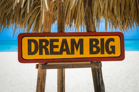Wooden sign board in beach with text: Dream big