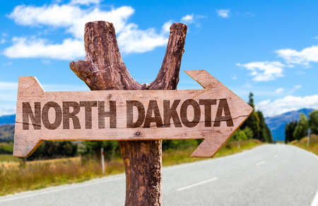 North Dakota sign with arrow on road background Stock Photo