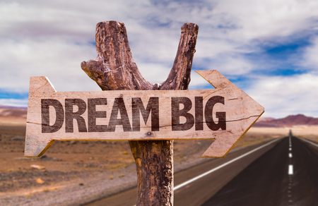 Dream big sign with arrow on road background Stock Photo