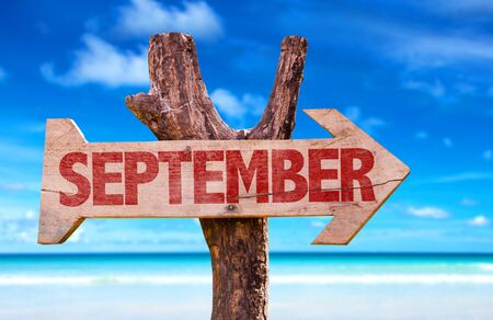 September sign with arrow on beach background