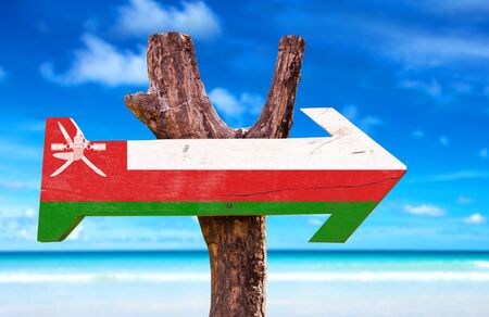 oman background: Oman flag sign with arrow on beach background